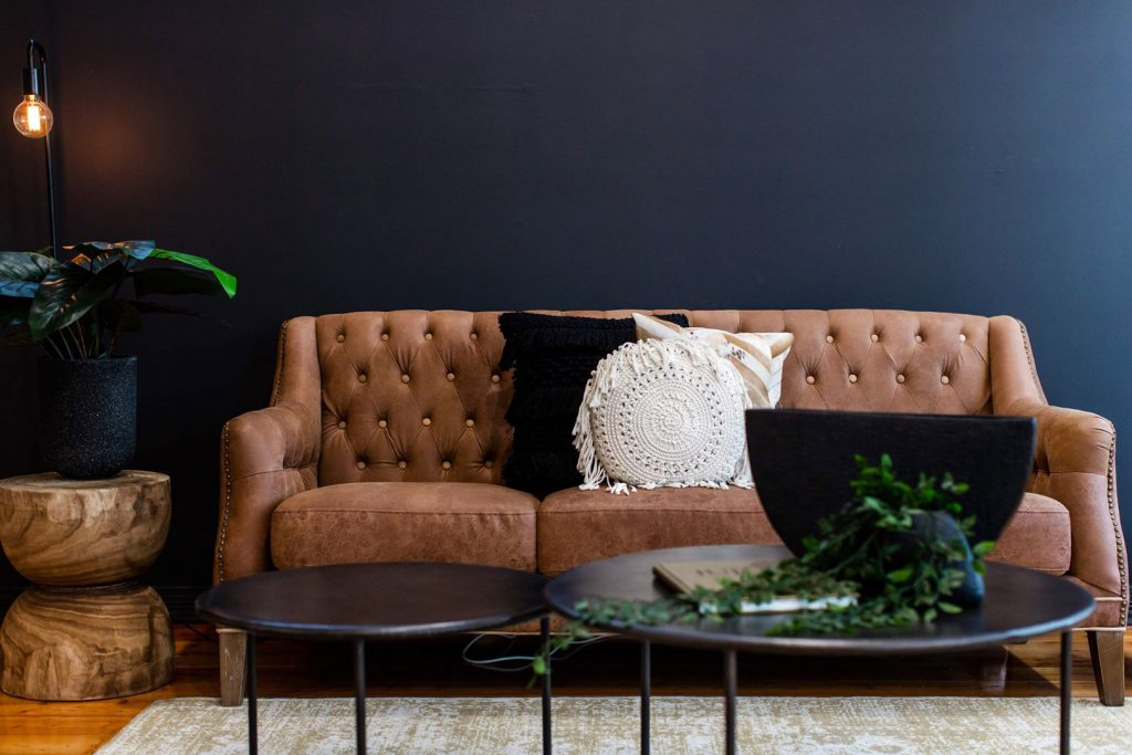 Two round coffee tables in front of brown leather lounge with brown and white pillows